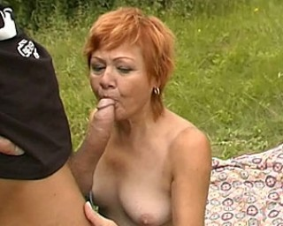 Mature redhead sucking and fucking in the grass